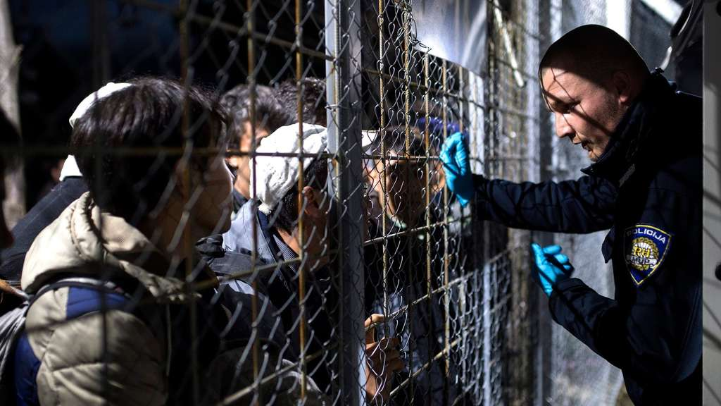 epa05175693 A Croatian police officer talks to refugees from Syria and Iraq waiting to cross the Greek-Macedonian border, near the Macedonian city of Gevgelia, The Former Yugoslav Republic of Macedonia, 22 February 2016. Macedonia confirmed that it is only allowing Syrian and Iraqi refugees through, matching a decision by its northern neighbour, Serbia. Around 5,000 people were waiting at the border on 22 February, local reports said, quoting witnesses. All want to continue their journey across Macedonia, Serbia, Croatia, Slovenia and then Austria, with Germany the final goal for most. EPA/GEORGI LICOVSKI +++(c) dpa - Bildfunk+++