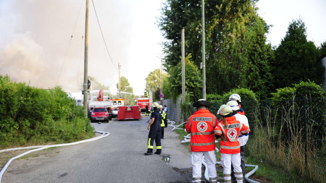 Die Feuerwehr löscht einen Brand in einer Autoverwertungsanlage