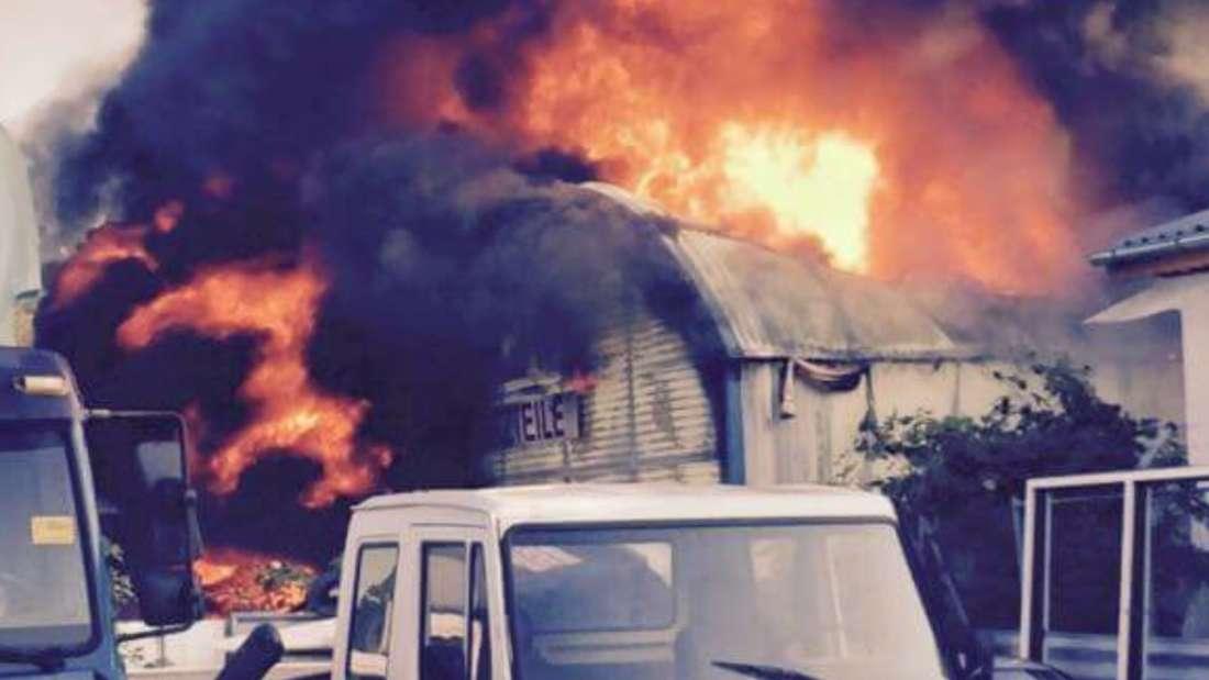 Aus der Autoverwertungsanlage in Rheingönheim schießen die Flammen. Dicke Rauchschwaden bilden sich.