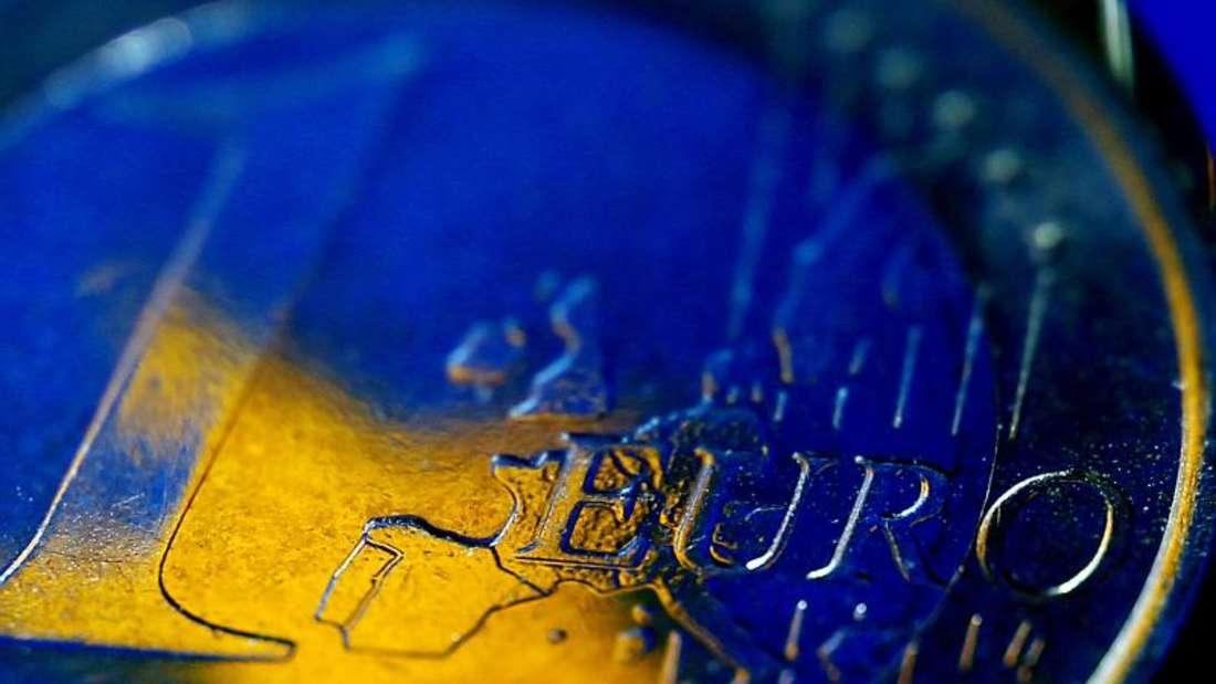 Die Fahne der Europäischen Union spiegelt sich in einer Euro-Münze. Europa schützt mit einem Notfalltopf für Pleitebanken künftig die Steuerzahler vor Milliardenkosten. Foto: Oliver Berg