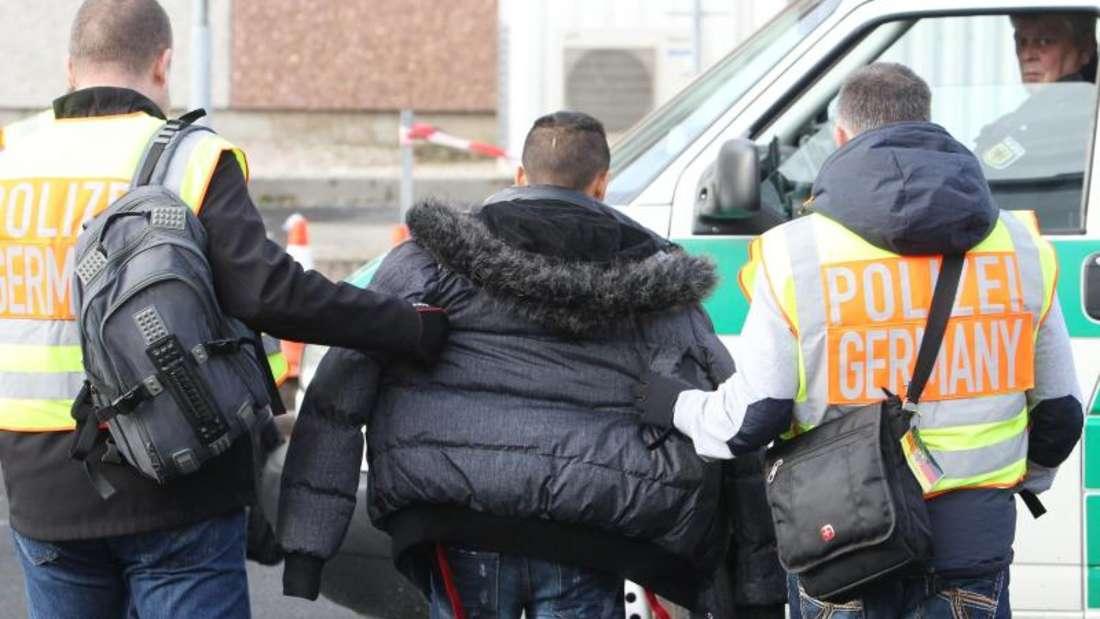 Polizisten begleiten einen straffällig gewordenen Asylbewerber zu seinem Abflug. Foto: Sebastian Willnow/Archiv