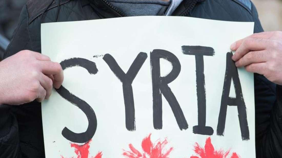 Ein syrischer Flüchtling hält während einer Kundgebung ein Transparent in den Händen. Er möchte auf die leidende Bevölkerung der belagerten syrischen Stadt Madaja aufmerksam machen. Foto: Sebastian Kahnert