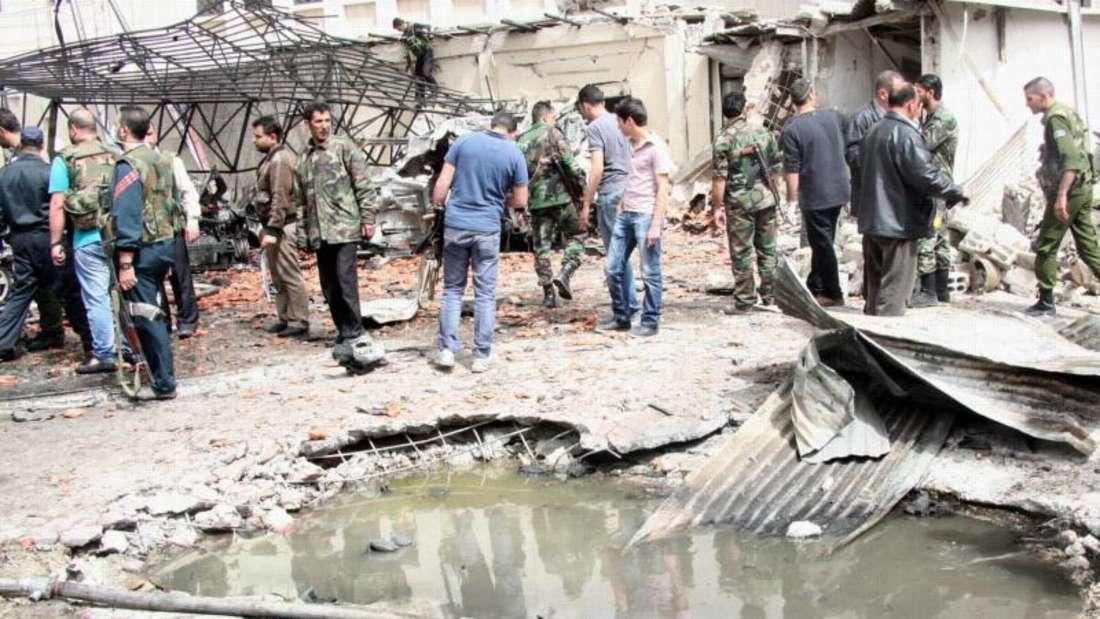 Soldaten und Anwohner am Ort eines Bombenanschlags in Damaskus. Foto: Youssef Badawi / Archiv