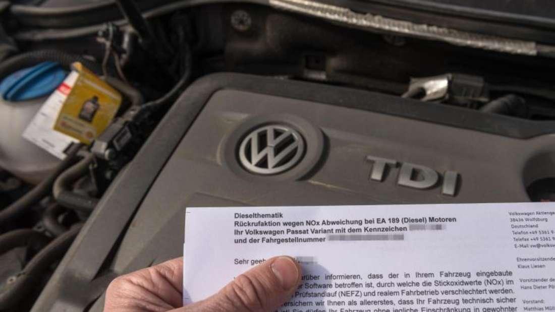 Ein Brief von Volkswagen zur Rückrufaktion zum Abgas-Skandal vor den Motor eines VW Passat Diesel. Foto: Armin Weigel