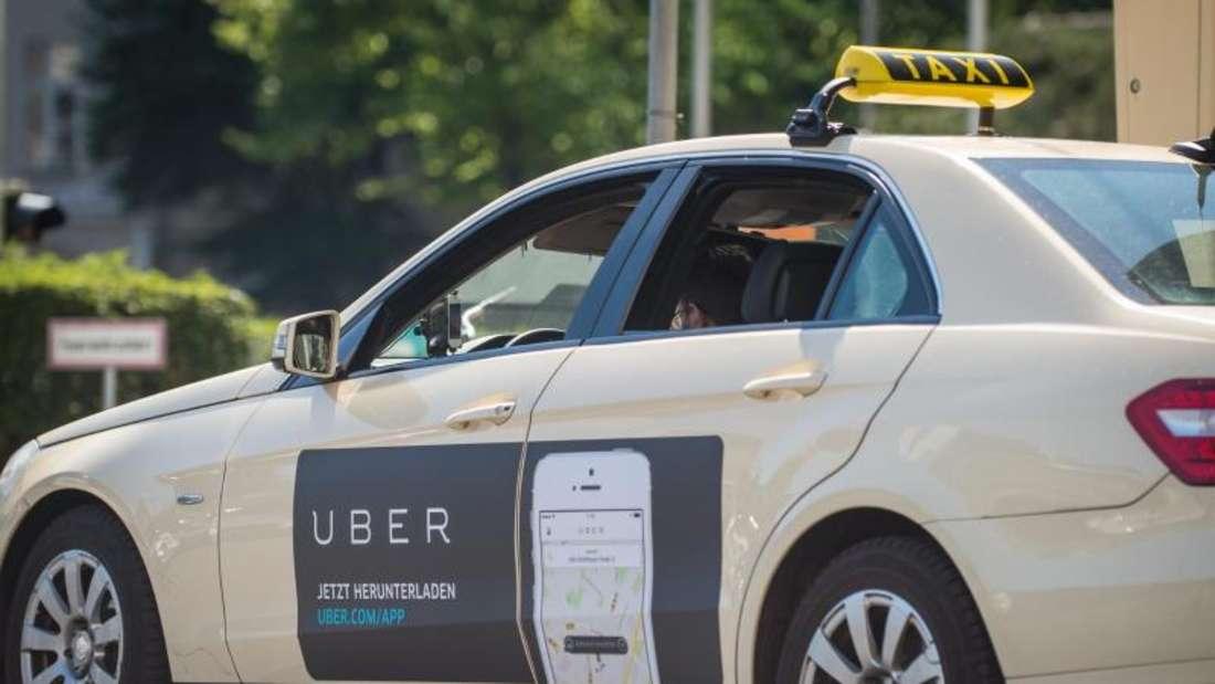 Ein Taxi mit Werbung der App «Uber». Foto: Florian Gaertner/Archiv