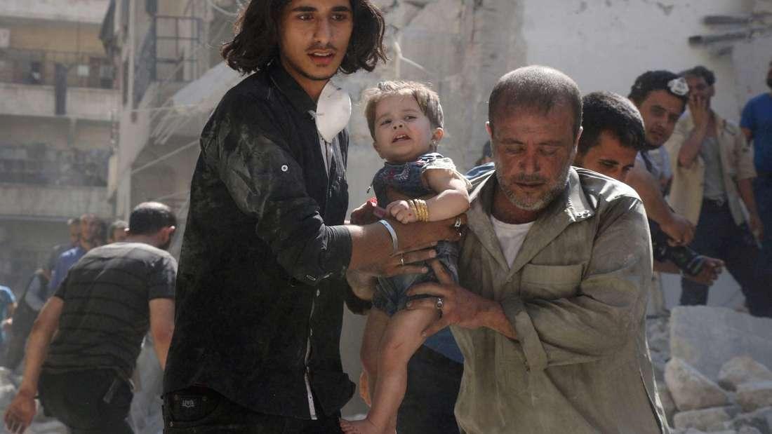 Ein kleines Kind wird in Aleppo aus den Trümmern gerettet.