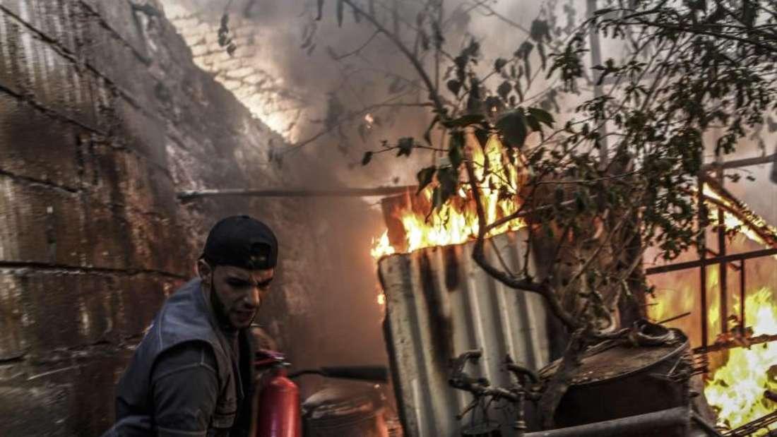 Ein brennendes Gebäude nach einem Luftangriff auf einen vonRebellen gehaltenen Vorort vonDamaskus. Foto: Mohammed Badra