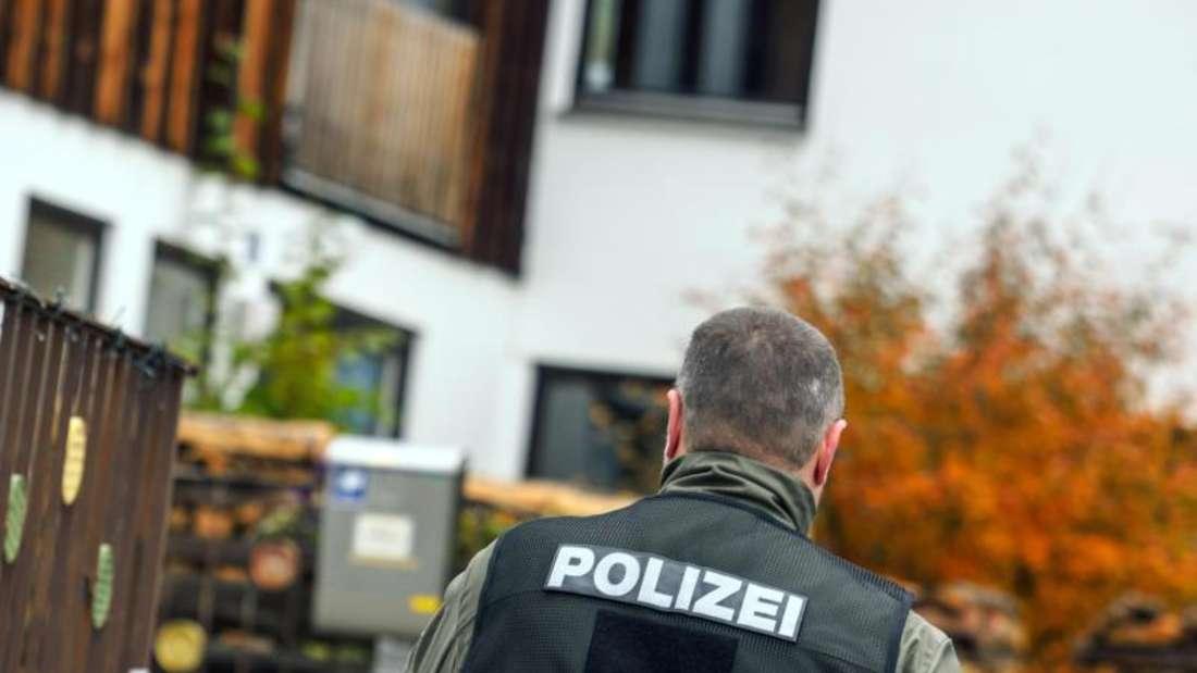 Ein Polizist geht vor einem Haus entlang, in dem ein Angehöriger der Reichsbürger-Bewegung bei einer Razzia vier Polizisten durch Schüsse zum Teil schwer verletzt hatte. Foto: Nicolas Armer/Archiv
