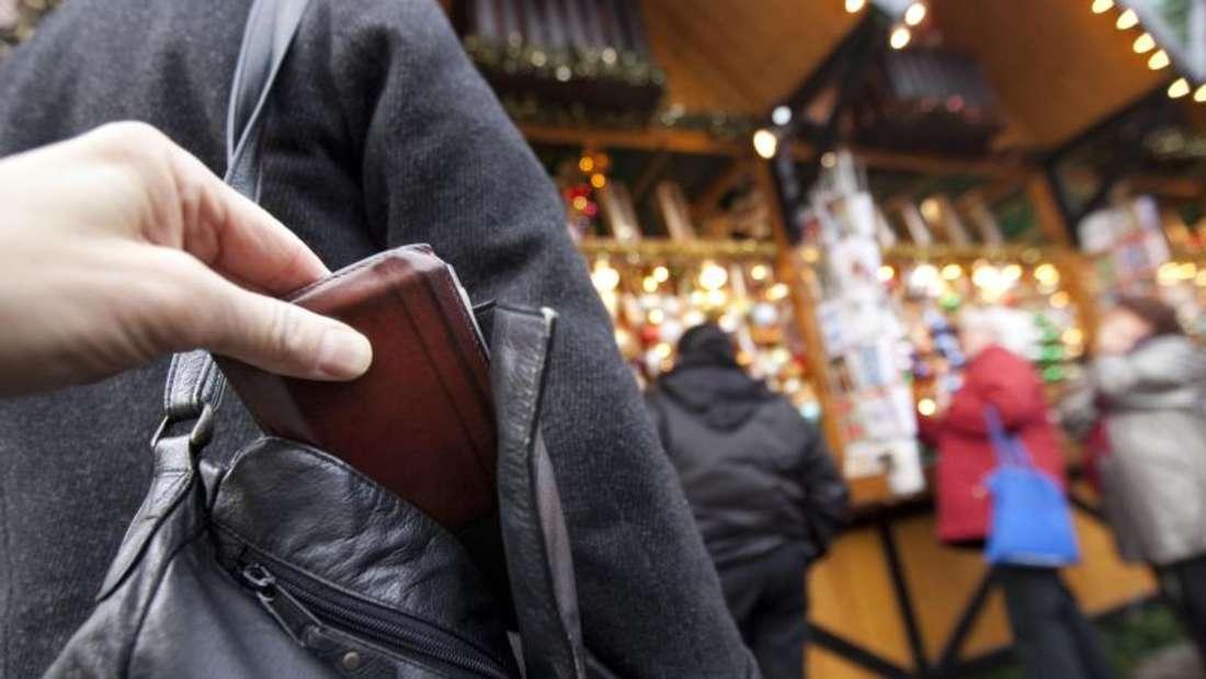 Ein Mann zieht einer Passantin die Geldbörse aus der Handtasche. Foto: Frank Rumpenhorst/Illustration
