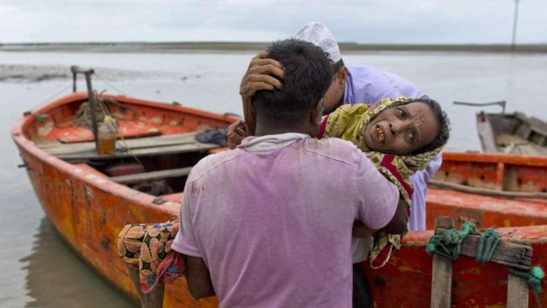 Freiwillige helfen in Teknaf (Bangladesch) einer älteren Rohingya-Frau, die aus Myanmar geflüchtet ist. Foto: Gemunu Amarasinghe