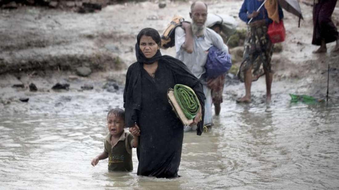 Eine Frau der muslimischen Minderheit der Rohingya durchquert in Bangladesch mit ihrem Sohn einen Kanal. Foto: Km Asad/ZUMA Wire