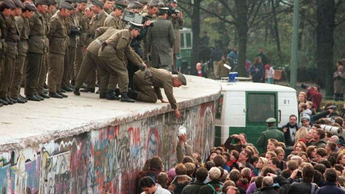 Da herrschte noch eitelSonnenschein:Das Foto vom 11.November 1989 zeigt einen DDR-Grenzposten, der von Demonstranten eine Kanne Kaffee auf die Mauer vor dem Brandenburger Tor gereicht bekommt. Foto: Archiv