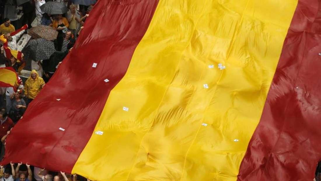 Demonstranten tragen in Barcelona bei einer Demonstration gegen die Unabhängigkeit Kataloniens eine riesige spanische Flagge. Foto: Manu Fernandez