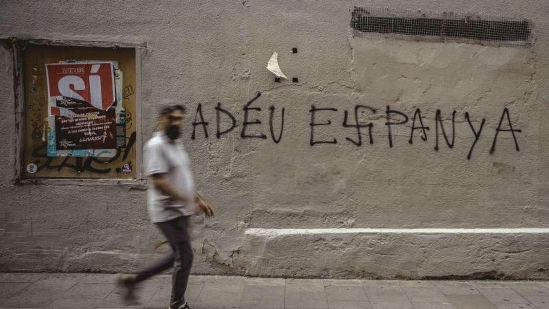 Ein Mann geht in Barcelona an einer Mauer vorbei, auf der auf Katalansich «Auf Wiedersehen Spanien» steht. Das «s» ist als Hakenkreuz geschrieben. Foto: Matthias Oesterle