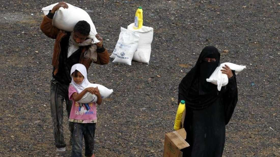 Es gibt Nahrung:Jemeniten tragen ihre Essensrationen nach Hause. Foto: Yahya Arhab