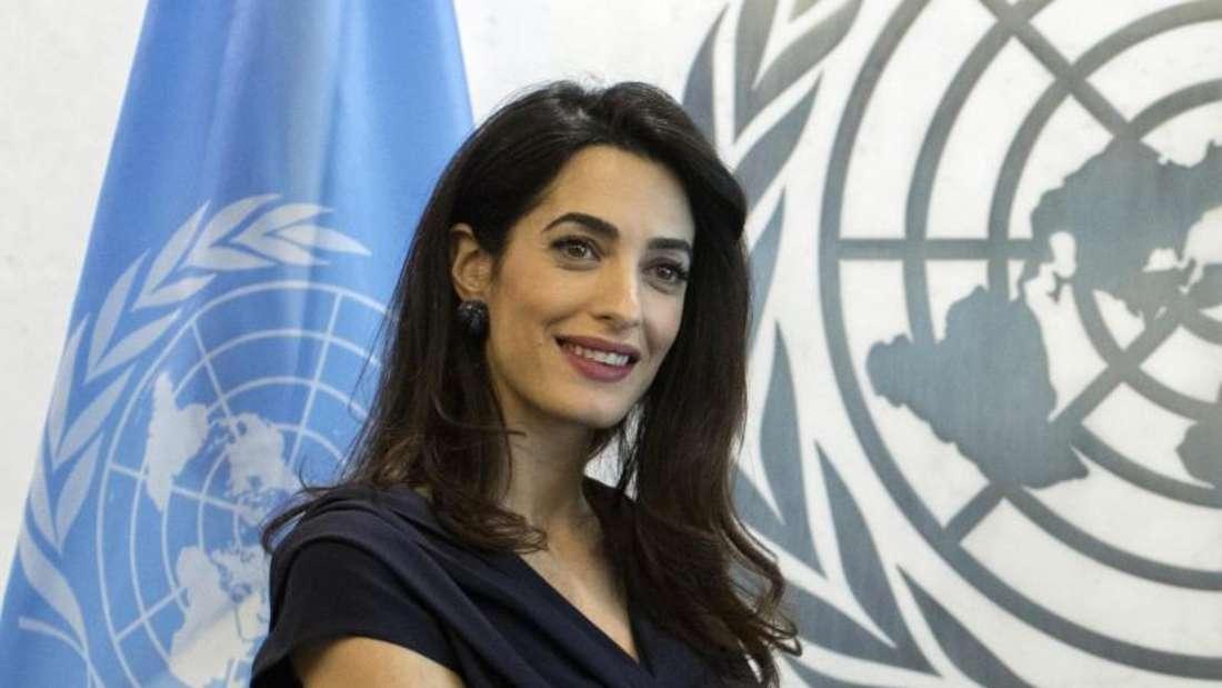 Rechtsanwältin Amal Clooney vor dem Logo und der Fahne der UN. Foto: Mary Altaffer