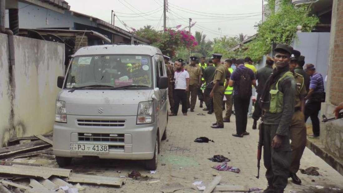 Polizisten und Soldaten sichern die Straße vor einem Haus. Foto: Achala Upendra/AP