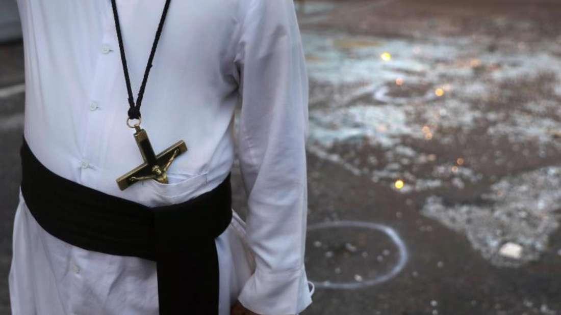 Nach den Anschlägen:Ein katholischer Priester steht neben Glasscherben in Colombo. Foto: Manish Swarup/AP