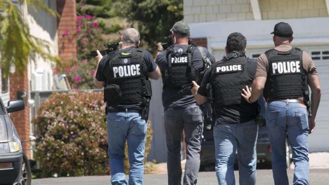 Schwer bewaffnete Polizisten aus San Diego nähern sich einem Haus, in dem der Täter eines Anschlags auf die Chabad of Poway Synagoge vermutet wird. Foto: John Gibbins/The San Diego Union-Tribune/AP