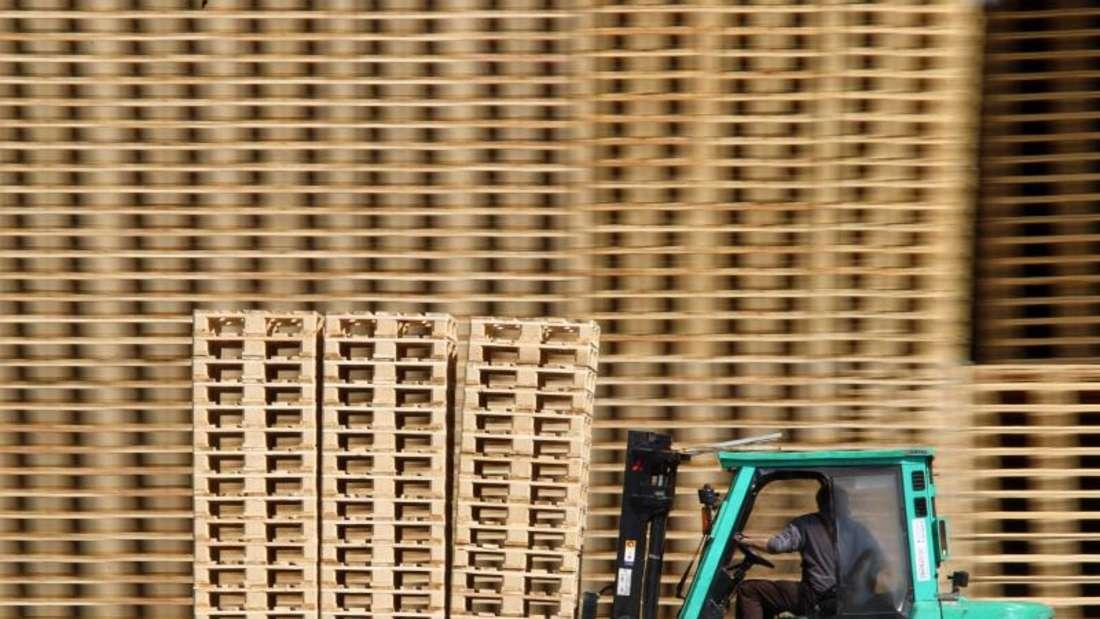 Ein Mann fährt mit einem Gabelstapler an Holzpaletten vorbei. Foto: Jens Büttner