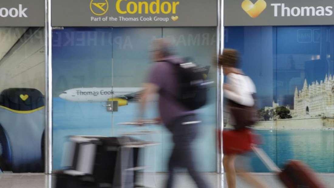 Passagiere gehen an einem Büro von Condor und Thomas Cook am Flughafen Palma de Mallorca vorbei. Foto: Clara Margais