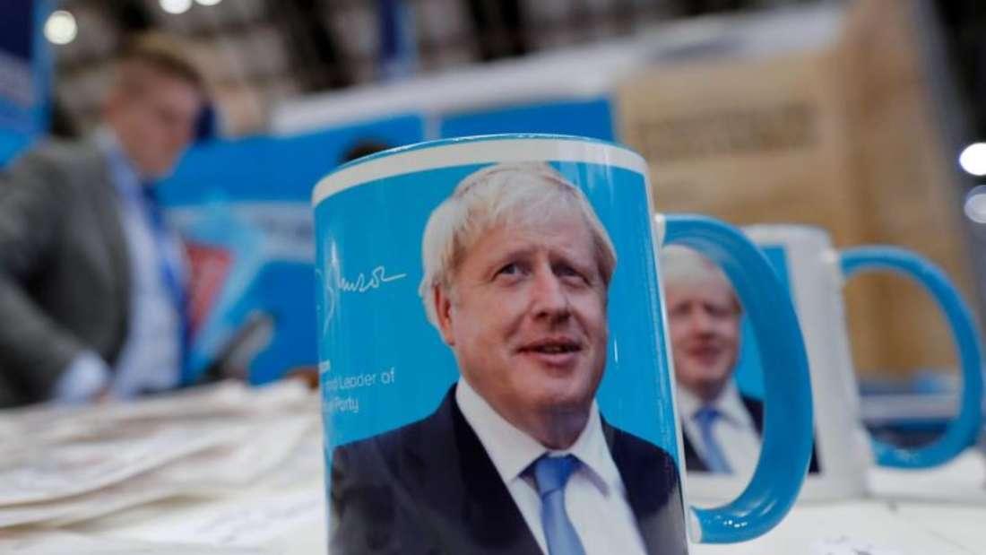 Tassen mit dem Gesicht von Premierminister Boris Johnson auf dem Parteitag. Foto: Frank Augsteink/AP