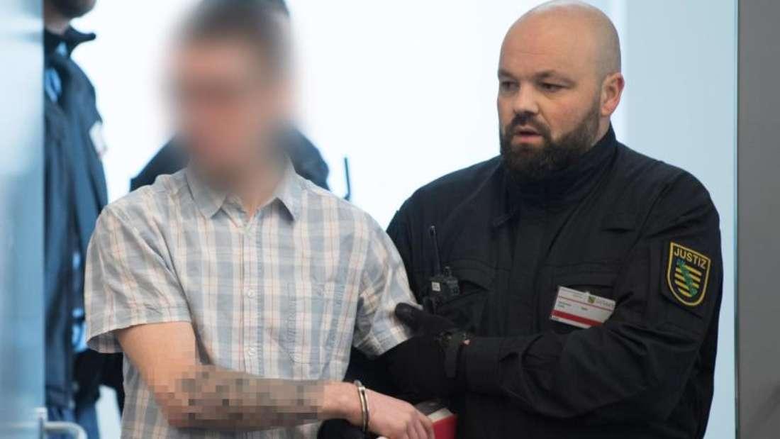 Ein Angeklagter wird im Oberlandesgericht Dresden zu Prozessbeginn in den Verhandlungssaal geführt. Foto: Sebastian Kahnert