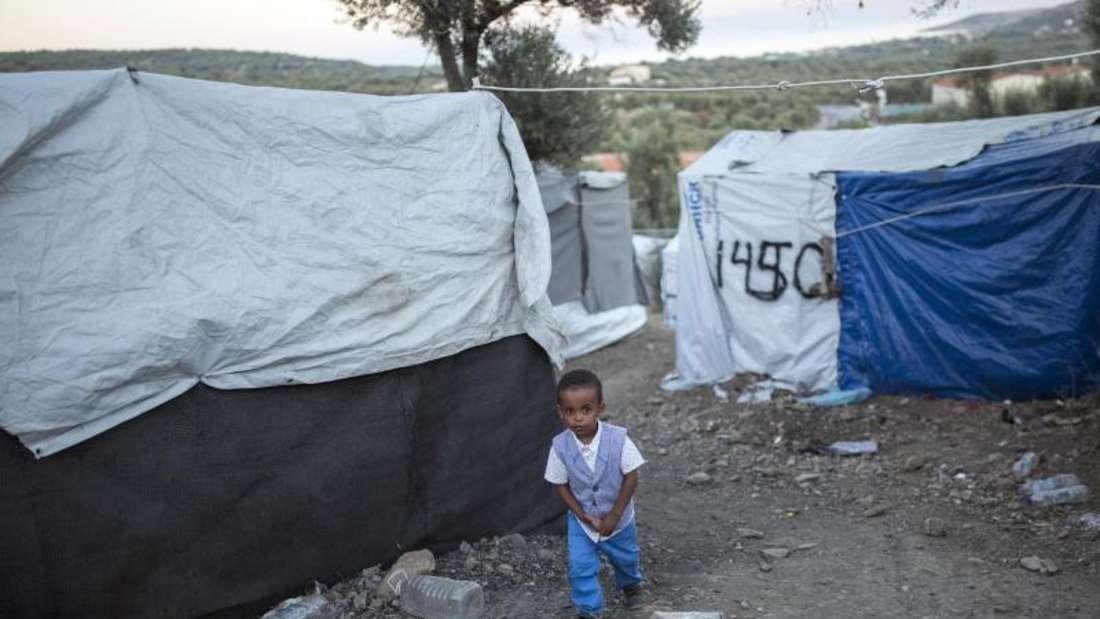 Ein Kind wandert in einem provisorischen Lager neben dem Flüchtlingslager Moria zwischen den Zelten entlang. Foto: Socrates Baltagiannis