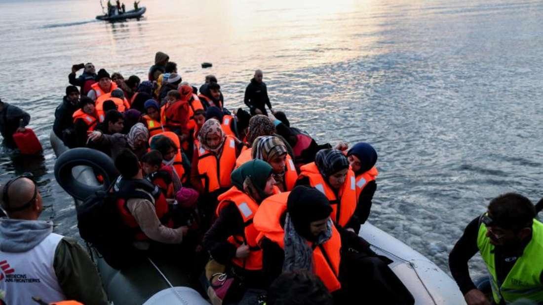 Freiwillige helfen auf Lesbos völlig erschöpften Flüchtlinge aus ihrem Boot. Foto: Kay Nietfeld