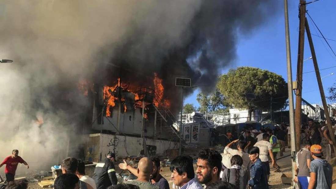 Migranten und Flüchtlinge stehen neben brennenden Hauscontainern. Foto:InTime News/AP