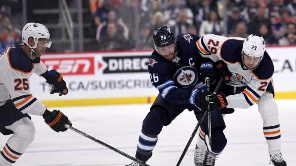 Blake Wheeler (M.) von den Winnipeg Jets im Zweikampf mit Leon Draisaitl (r). Foto: Fred Greenslade/The Canadian Press/AP/dpa