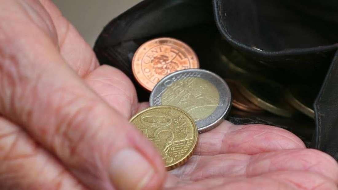 Eine Rentnerin hält einen Geldbeutel mit verschiedenen Euromünzen. Foto: Karl-Josef Hildenbrand/dpa