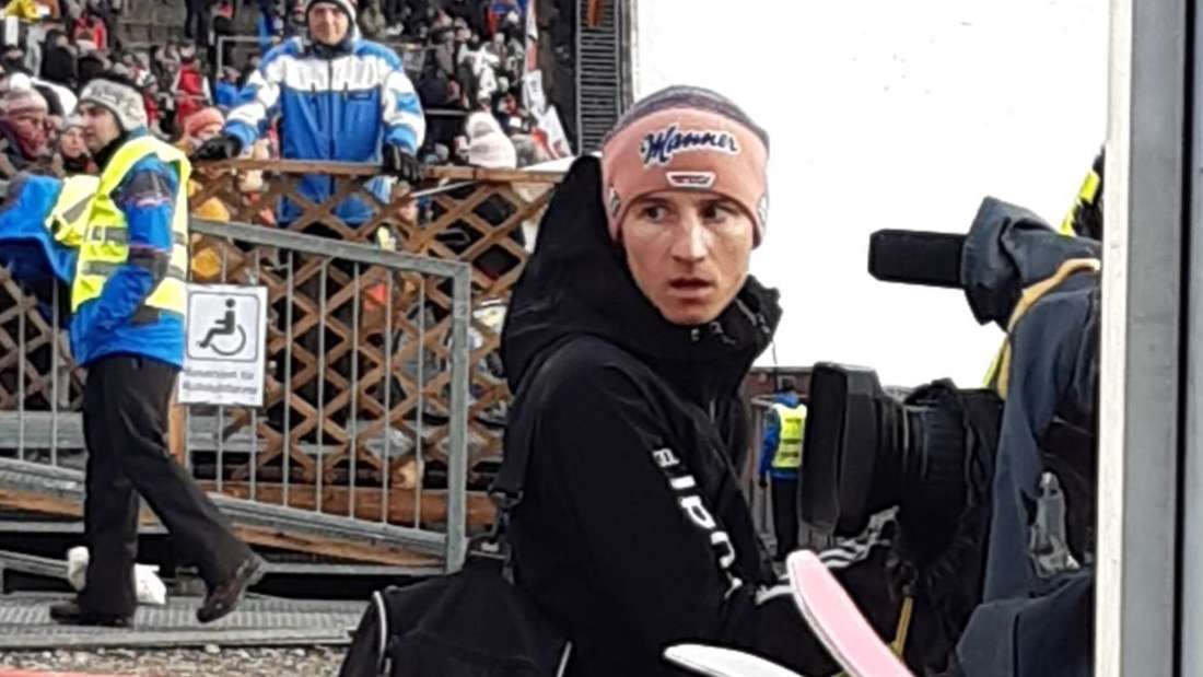 Qualifikation in Oberstdorf: Lokalmatador Karl Geiger packt sich in einen langen Mantel ein.
