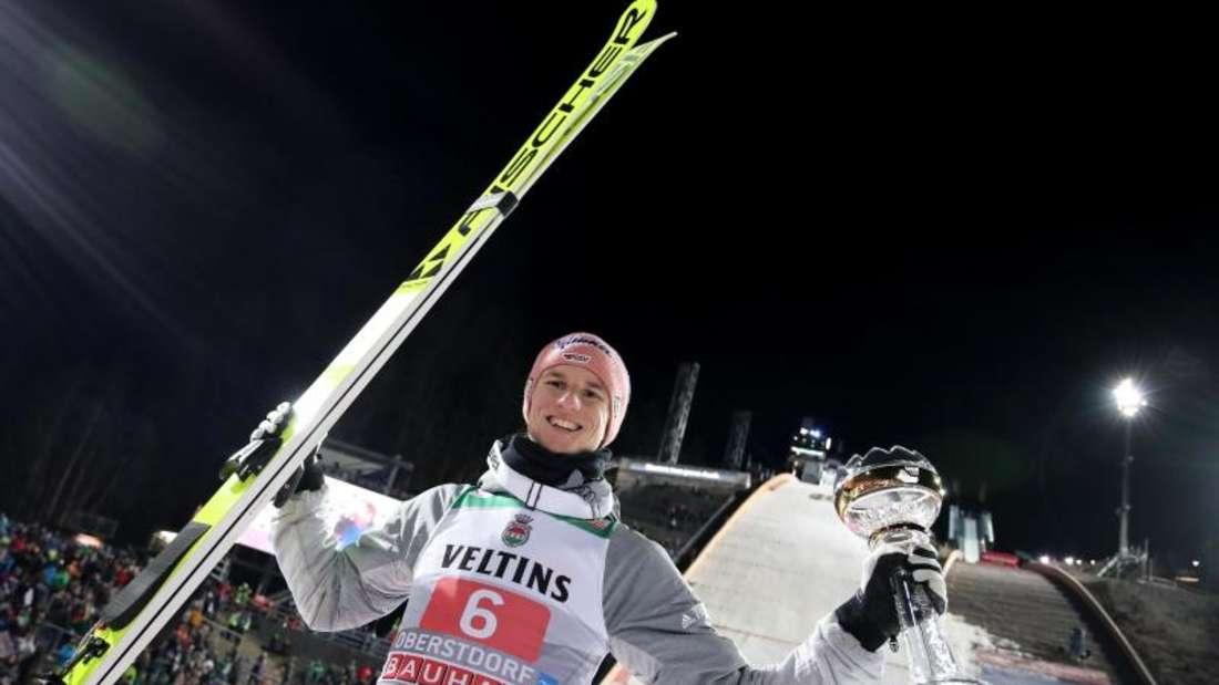 Karl Geiger jubelt mit dem silbernen Pokal für seinen zweiten Platz. Foto: Daniel Karmann/dpa