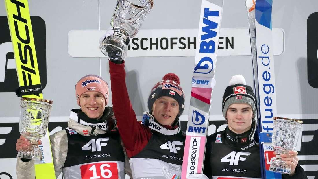 Springen in Bischofshofen: Karl Geiger (links), Dawid Kubacki (Mitte) und Marius Lindvik stehen auf dem Podest der Vierschanzentournee.