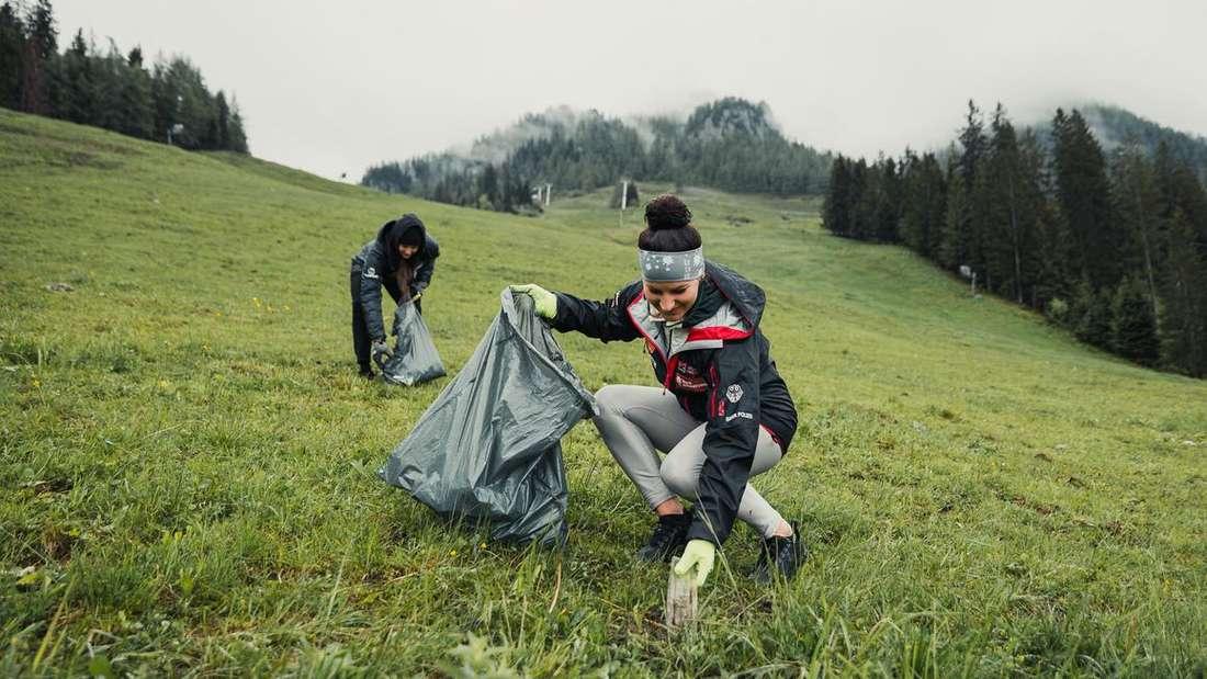 Die Weltcup-Fahrerinnen Ramona Hofmeister (vorne) und Cheyenne Loch sammeln beim Mountain Clean Up Müll am Jenner.