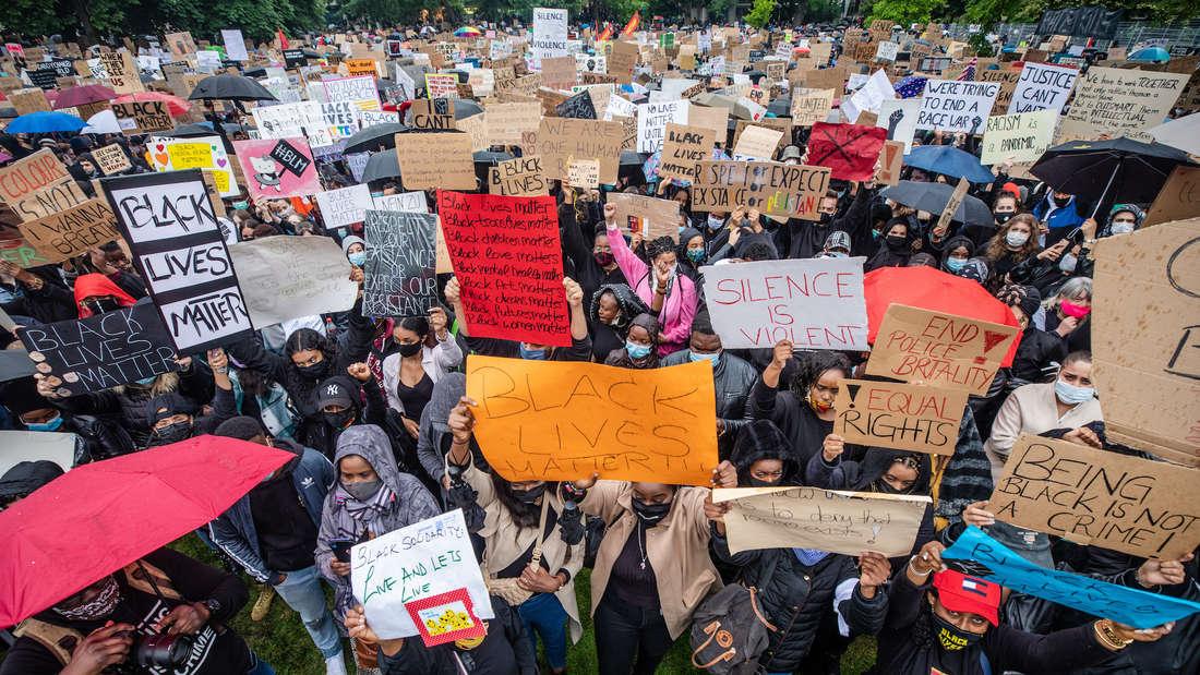 """Menschen halten Schilder mit der Aufschrift """"Black lives matter"""" hoch und demonstrieren gegen Rassiusmus."""