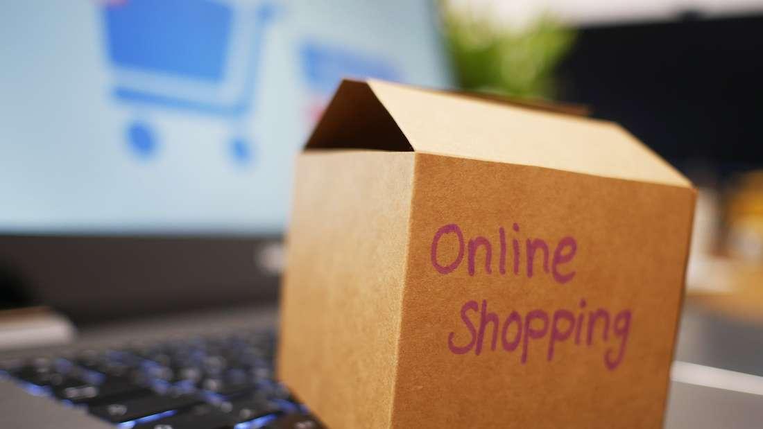 """Kleiner Karton mit der Aufschrift """"Online Shopping"""" befindet sich auf einem Laptop"""