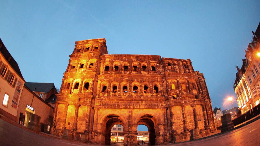 Das Wahrzeichen der Stadt, die Porta Nigra, wird am Abend in der Innenstadt von Scheinwerfern angestrahlt.