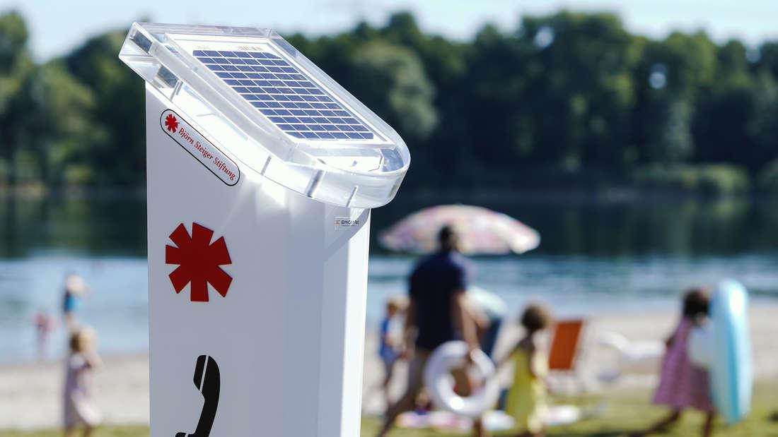 Eine Notrufsäule an einem See.
