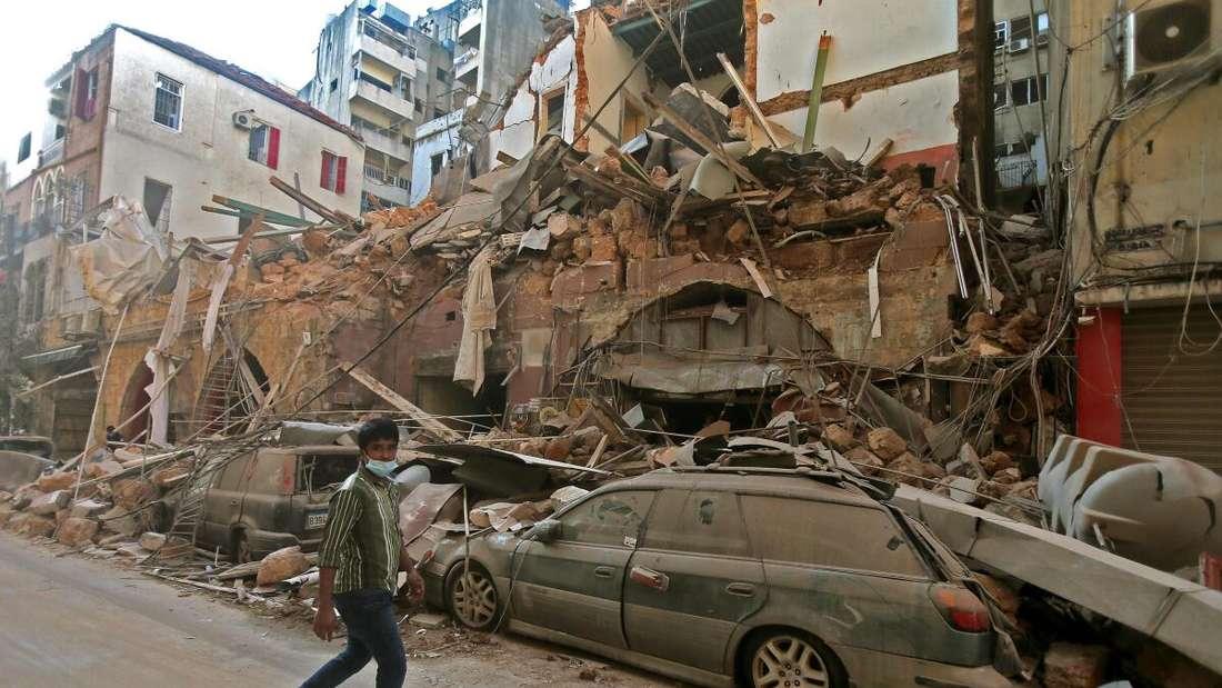 Ein Auto ist unter einem eingestürzten Gebäude begraben. Auf der Straße davor läuft ein Mann mit ernstem Gesicht und Corona-Schutz-Maske.