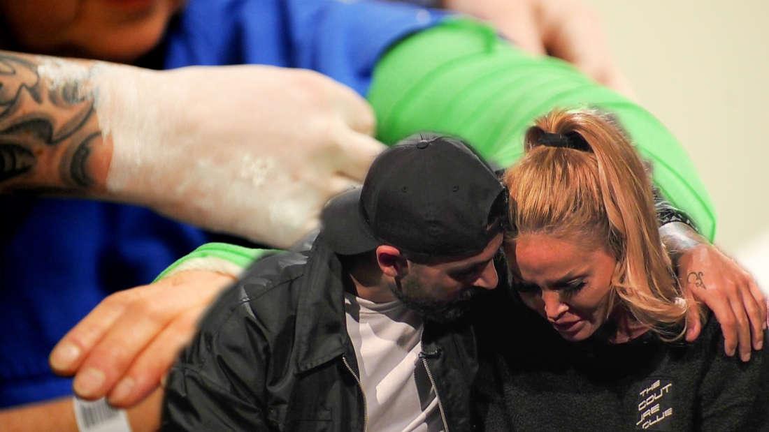 Lou umarmt Lisha. Im Hintergrund wird ein Arm eingegipst.