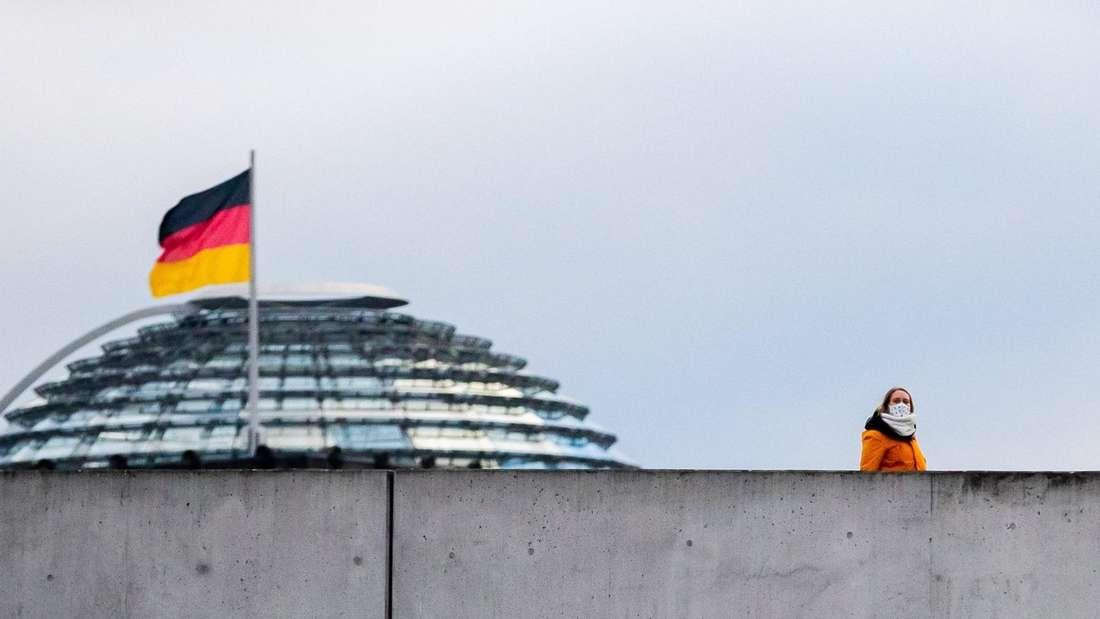 Eine Frau mit Mund-Nasen-Schutz geht im Regierungsviertel hinter einer Mauer vor der Kuppel des Reichstagsgebäudes entlang.