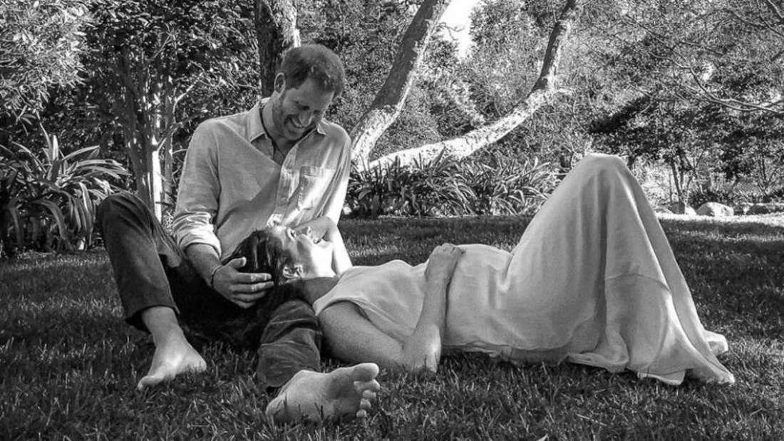 Harry sitzt barfuß im Gras, Meghan hat ihren Kopf auf seinem Schoß und legt liebevoll eine Hand auf ihren gewölbten Bauch.