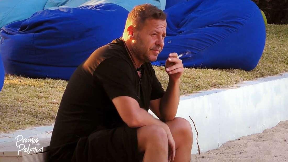 """Willi Herren mit einer Zigarette am Strand von """"Promis unter Palmen"""""""