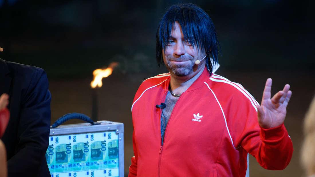 Ikke Hüftgold im roten Trainingsanzug und Perücke in einer TV-Show