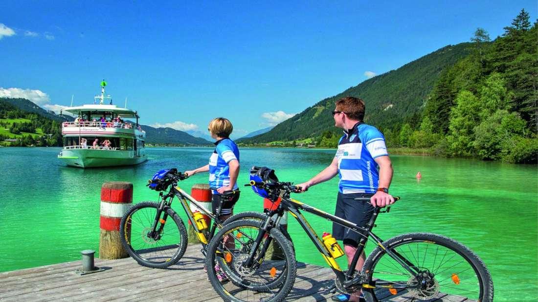 Radfahrer warten auf ein Schiff am Weißensee in Kärnten (Österreich).