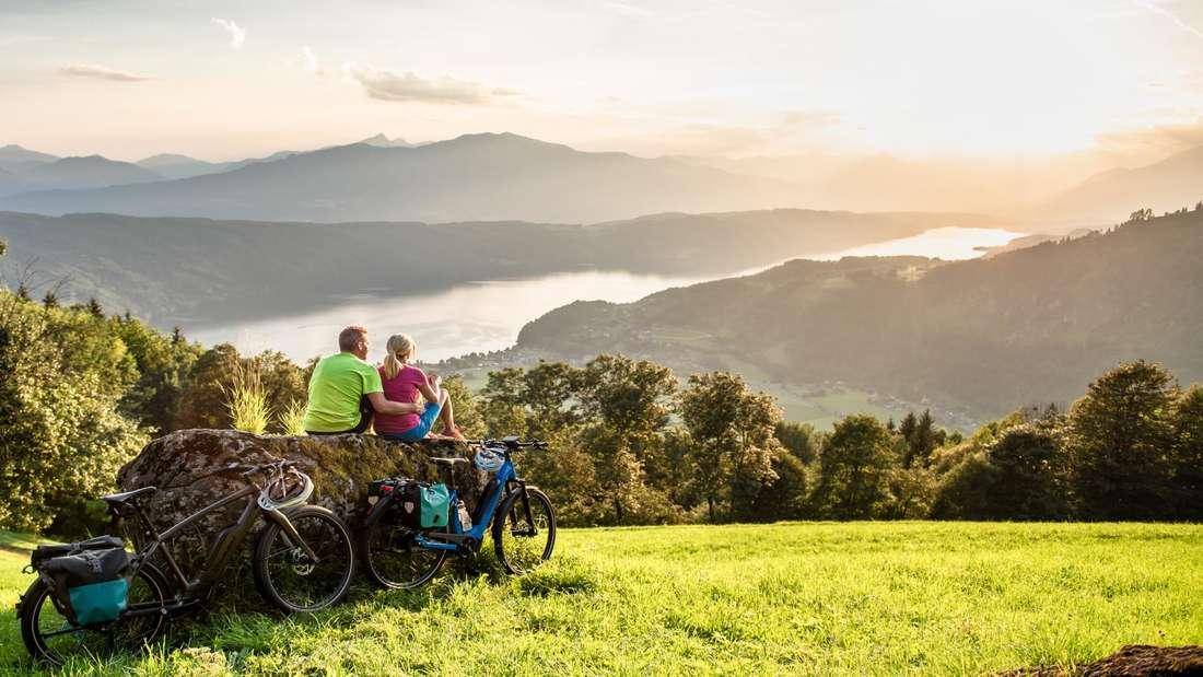 Radfahrer genießen den Blick über die Natur in Kärnten.