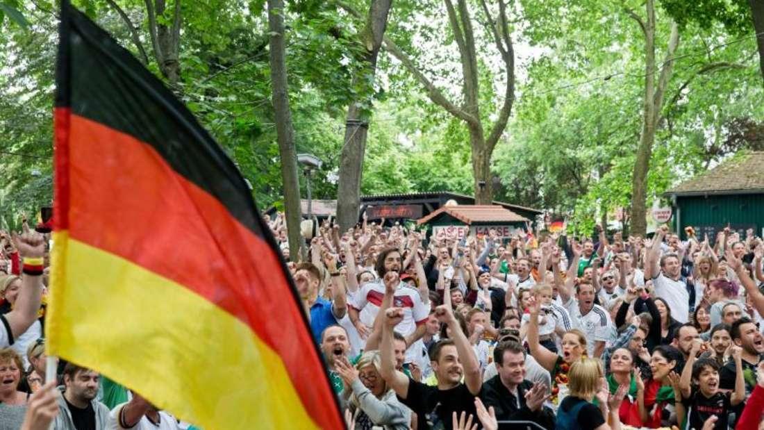 Fans jubeln während der Übertragung eines WM-Spiels in einem Biergarten.Foto: Daniel Karmann/Archiv