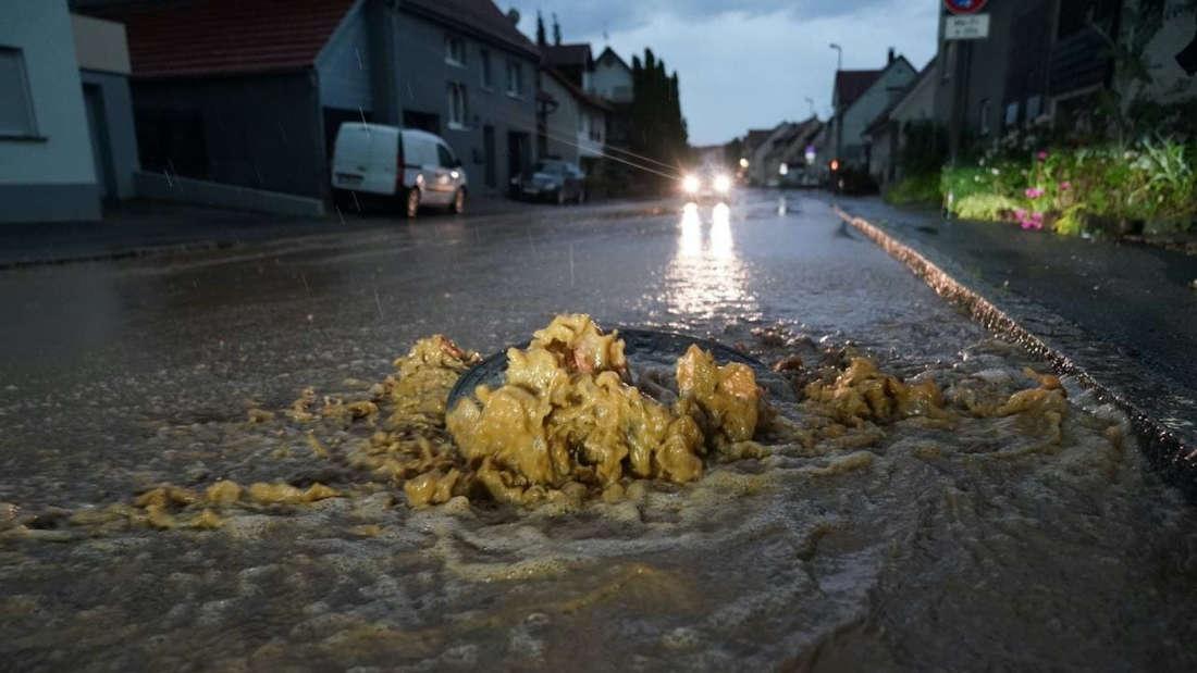 Eine Straße ist überflutet, das Wasser kommt aus einem Gulli.